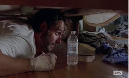 Rick (Andrew Lincoln) hides under the bed in Season 4, Episode 11 of AMC's The Walking Dead